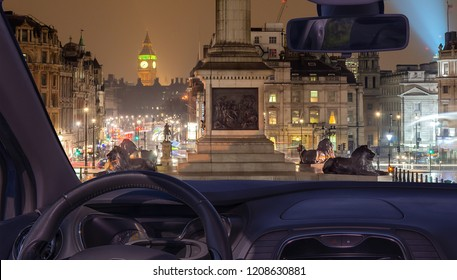 Looking through a car windshield with view of Trafalgar Square at night with the Big Ben on the background, London, UK
