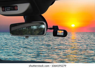 Looking through a dashcam car camera installed on a windshield with view of a scenic sunset on the mediterranean sea