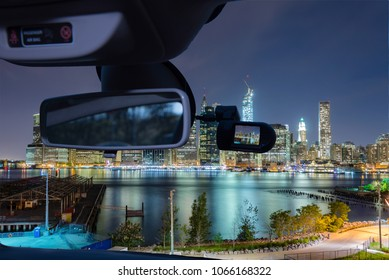 Looking through a dashcam car camera installed on a windshield with view of Manhattan skyline at night, New York City, USA