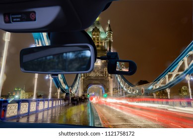 Looking through a dashcam car camera installed on a windshield with view of Tower Bridge at night, iconic landmark in London, UK