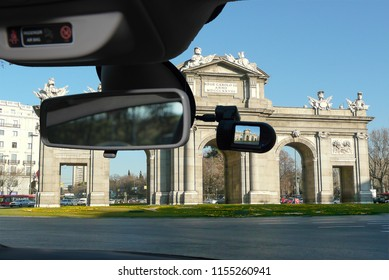 Looking through a dashcam car camera installed on a windshield with view of Alcala Gate in the Independence Square, iconic landmark in Madrid, Spain