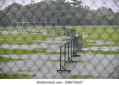 Looking through a deep green wired fence from the stadium, seeing a flooded football field filled with water in the raining season.