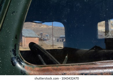 Looking through the dirty window of an abandoned car towards the ghost town of Bodie, California.