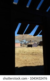 Looking through a doorway to buildings and the mine in Bodie, California