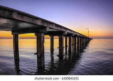 Looking through Dromana pier on sunset