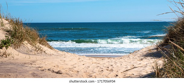 Looking through the dunes at the Atlantic Ocean on a sand footpath in Montauk New York Long Island USA.
