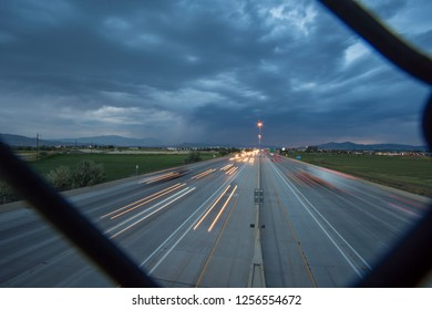 Looking through fence at traffic on freeway at night
