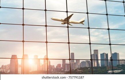 looking through the glass wall of airport when the airplane fly over modern cityscape with sunset