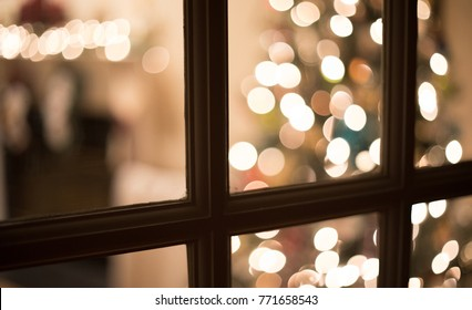 Looking through glass window panes at the Christmas tree and fireplace mantle.  Shallow depth of field so the tree and mantle are out of focus.