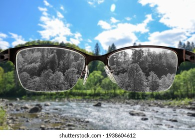 Looking through glasses to black and white river and forest landscape focused in women's glasses. Color blindness. World perception during depression. Medical condition. Health and disease concept.
