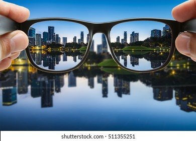 Looking through the glasses focus on city background reflection on the water, close up.