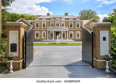 Looking through grand entrance gates to an elegant modern mansion