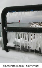 Looking through an icicle filled railing to a red lighthouse in the distance.