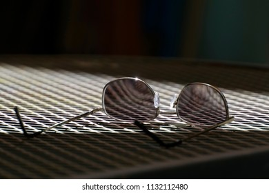Looking through the lenses of a pair of glasses shows the table's mesh pattern magnified and reflected curvature of the glass
