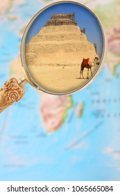 Looking through a magnifying glass or loop on a map of Africa showing Saqqara, Egypt's step pyramid.
