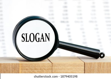Looking through a magnifying glass at the word Slogan, a business concept. Magnifying glass on the background of columns of numbers.
