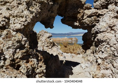 Looking through a natural rock window to Mono Lake, in northern California on a sunny afternoon.
