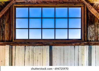 Looking through old rustic window of house with ocean view in Bonaventure Island, Quebec, Canada in barn