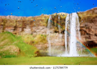 Looking through a raindrop covered window to a beautiful waterfall.