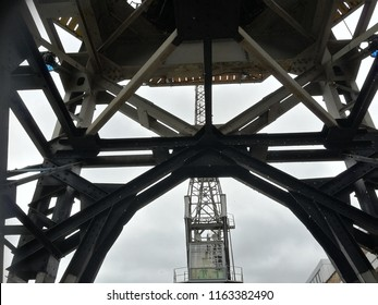Looking up through vintage harbor wharf crane to its neighbor.