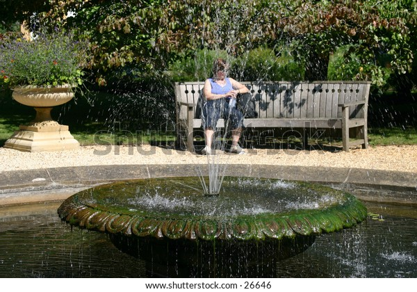 looking through the water of a fountain to a woman sitting on a bench