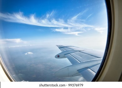 Looking through window aircraft during flight in wing with a nice blue sky