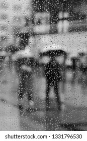 Looking through a window covered in rain drops and watching people walk by with umbrellas.