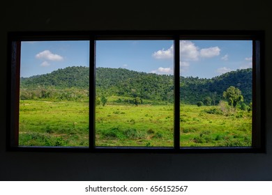 looking through the window frames to a peaceful panoramic mountain scene