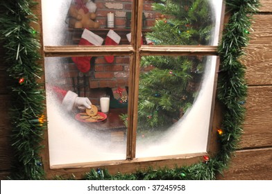 Looking Through the  window of a house as Santa Claus takes a cookie and and glass of milk.
