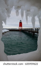 Looking through a window of ice at a red lighthouse in Charlevoix, Michigan.