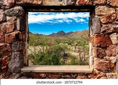 Looking through the window at the picturesque desert landscape from the ruins of a stone house on the Bowen Train in Tucson Arizona.