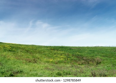 Looking at the top of a green hill with small yellow flowers against blue sky and wispy clouds. Room for text.