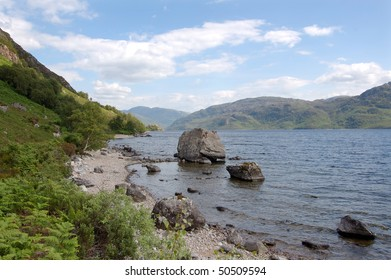 Looking toward the south Morar hills from the north shore of Loch Morar, Scotland with alarge rock on the loch foreshore