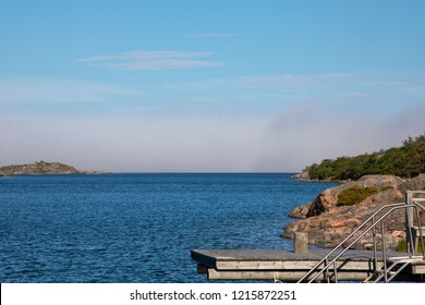 Looking towards a Baltic inlet in Kökar, a municipality of the Åland Islands, Finland, under a soft cloudy blue sky with a dark haze rolling in, during mid-morning near midsummer.