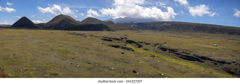 Looking towards Cotopaxi Volcano, Ecuador from the El Salitre Archaeological site with animals grazing on the paramo. and a lone car. Hummocks in mid distance are volcanic debris avalanche deposits.