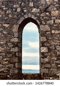 Looking towards the sea through historic arched window in Oban Scotland