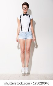 Looking trendy. Full length of beautiful young short hair woman in white shirt and suspenders jumping