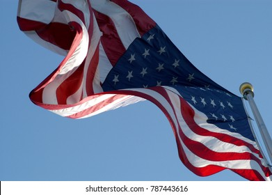 Looking up at United States Flag waving in the breeze. American flag on a flag pole waving in the wind against a blue sky, no clouds, no people. Looking up at US flag on a sunny day.
