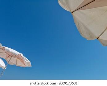 Looking upward at sky with beach umbrellas overhead.