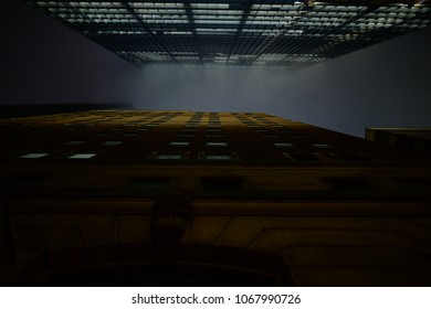 Looking upwards between new and old skyscrapers into a foggy sky at night. Looks dystopian, gothic and like something out of a noir or neo noir depiction of gotham city.