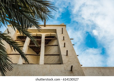 Looking upwards through the leaves of a palm tree towards a wind catcher, a traditional Arabian ventilation tower on a restored adobe building in the Arabian Gulf.