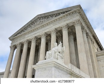 Looking up at the U.S. Supreme Court with justice statute in foreground