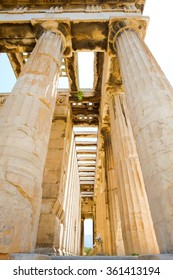 Looking up view of famous Greek temple pillars against clear blue sky in Greece