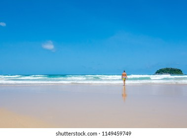 Looking at view point to seascape with blue sky and waves of kata beach with the man walking to the ocean ,One of the most famous beaches in Thailand at Kata beach ,PhuketThailand
