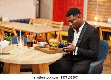 Looking at wallet to find cash for pay. Respectable young african american man in black suit sitting in restaurant with tasty double burger and soda drink.