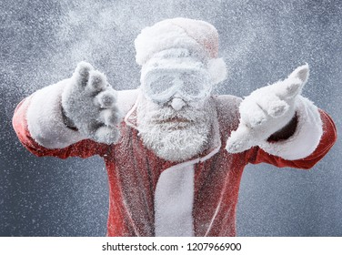 Looking for the way out. Waist up portrait of bearded old man in Santa costume getting stuck in the snowstorm