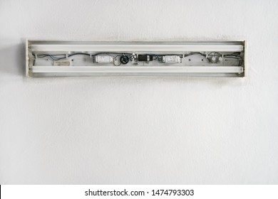 Looking up white ceiling in room, old neon lamp with no cover, cables and inside tubes visible