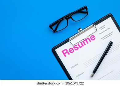 Looking for work concept. Resume on pad near pen and glasses on blue background top view space for text