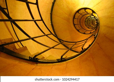 Looking up at a yellow colored spiral staircase that lookalike a nautilus shell in the arc de triumph in paris france
