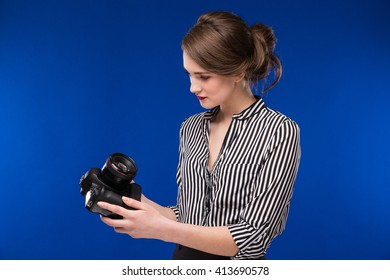 looking young brunette girl in the hands of the camera in a black shirt on a blue background